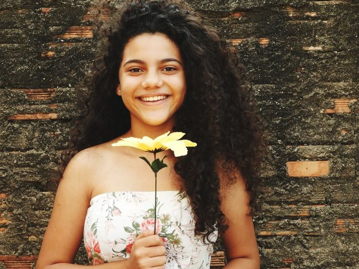 Portrait of smiling teenage girl with artificial flower standing against brick wall