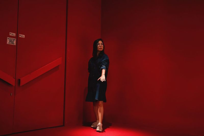 Full length of young woman standing against red wall