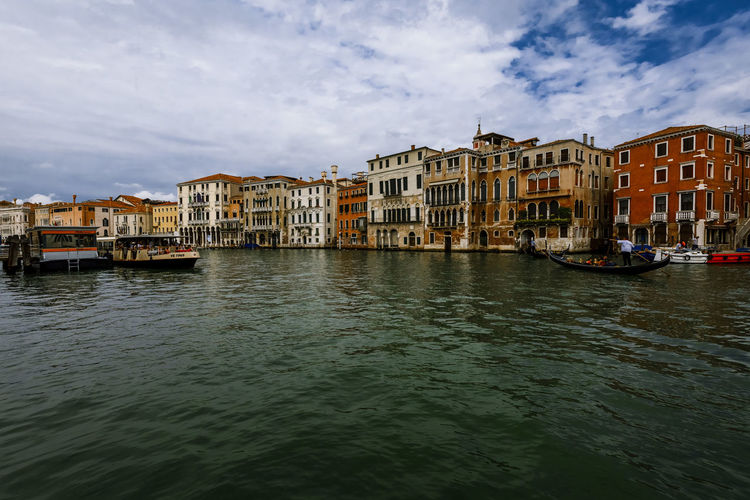 Buildings by grand canal against cloudy sky
