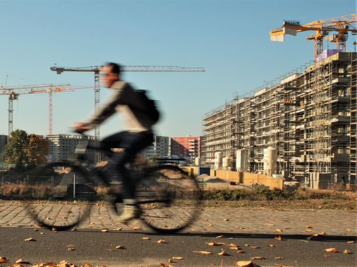 Construction Site Architecture Bicycle Bicycling Blurred Motion Building Exterior Built Structure City Day Land Vehicle Lifestyles Men Mode Of Transportation Motion Nature One Person Outdoors Real People Riding Sky