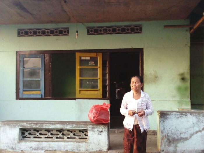 Mature woman standing outside house
