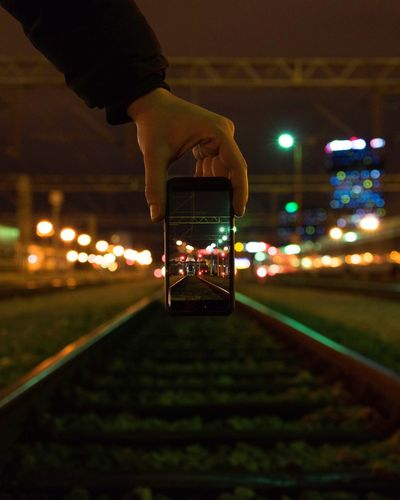 Man using smart phone on illuminated railroad tracks at night