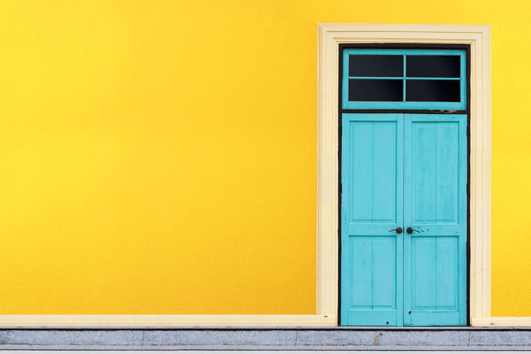 Closed blue doors of yellow building