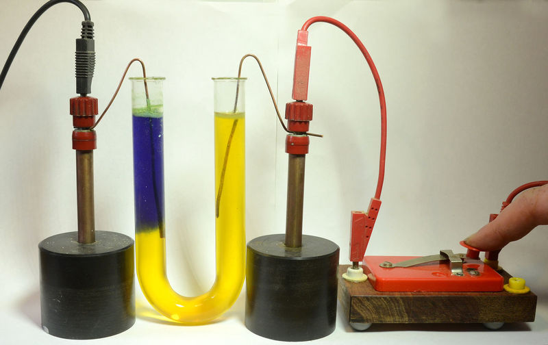 Current trough a liquid causes a pH indicator to change. Experiment Liquid Science Switch Blue Chemistry Close-up Dissociation Electrolysis Human Hand Inidcator Ions Multi Colored U Tube Yellow
