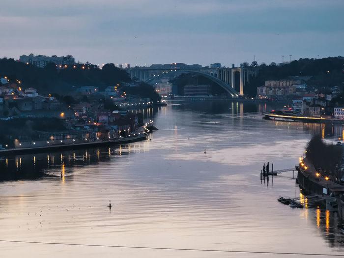 Bridge over river in city against sky at dusk