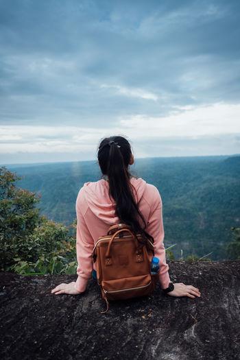 Rear view of women sitting on rock