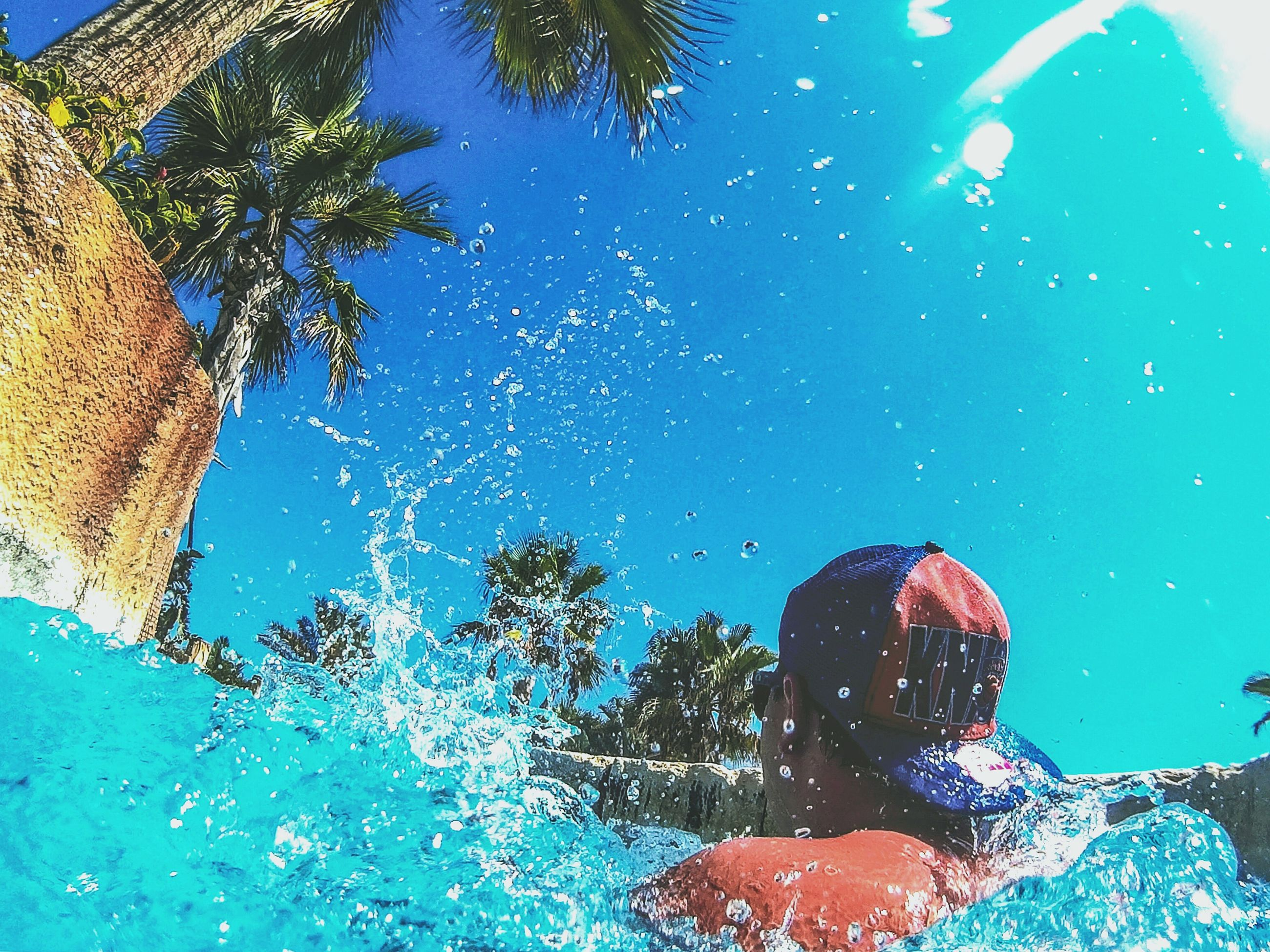 blue, building exterior, water, architecture, built structure, swimming pool, low angle view, clear sky, tree, outdoors, reflection, house, sky, turquoise colored, no people, day, underwater, residential building, nature, sunlight