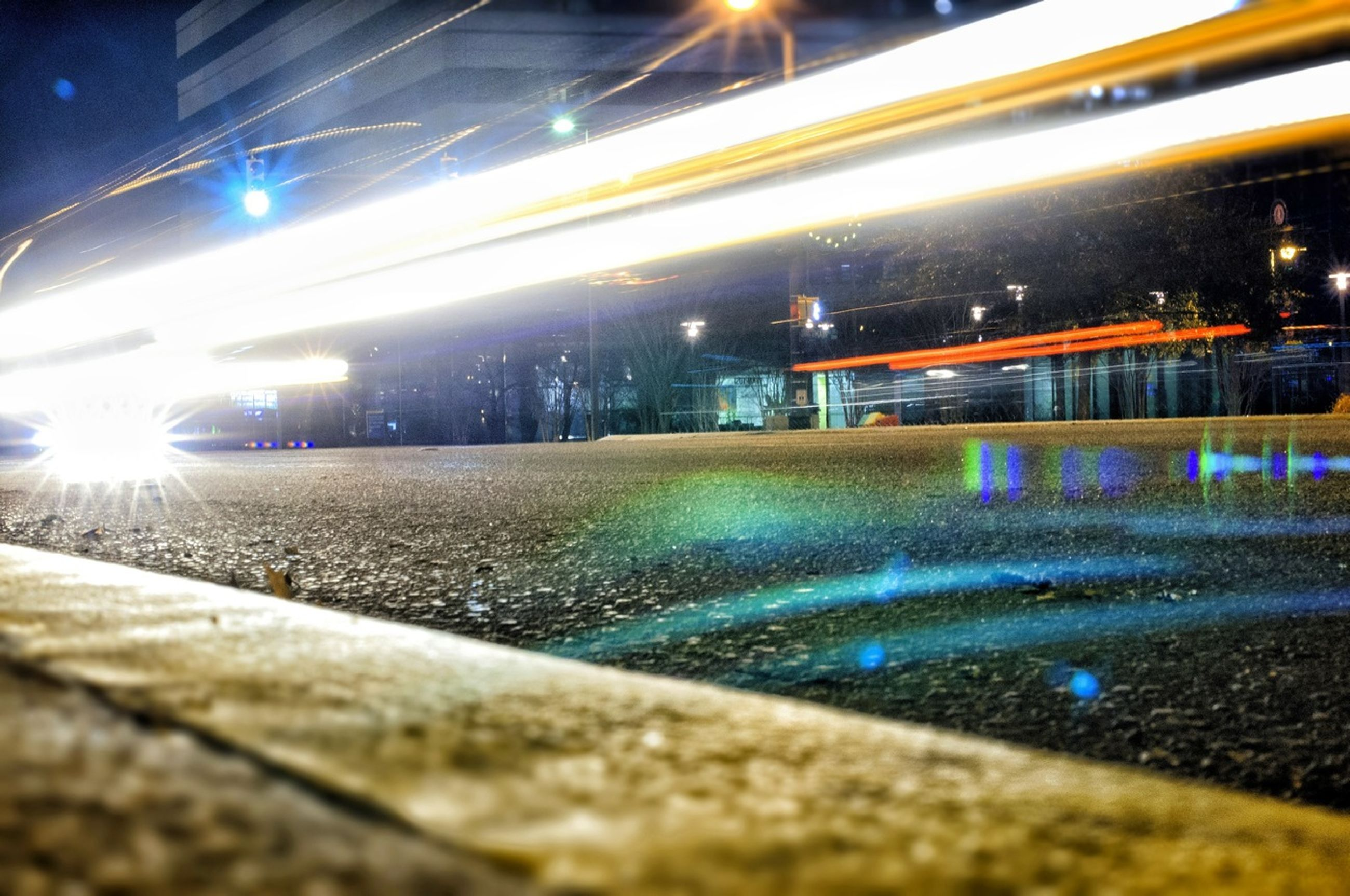 illuminated, night, city, light trail, transportation, long exposure, motion, speed, surface level, blurred motion, built structure, road, building exterior, architecture, street, water, city life, on the move, high angle view, light - natural phenomenon