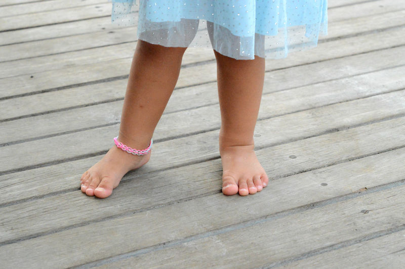 Low section of girl standing on wooden floor