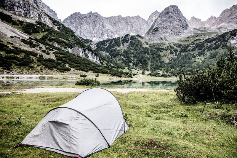 Tent By Lake Against Mountains