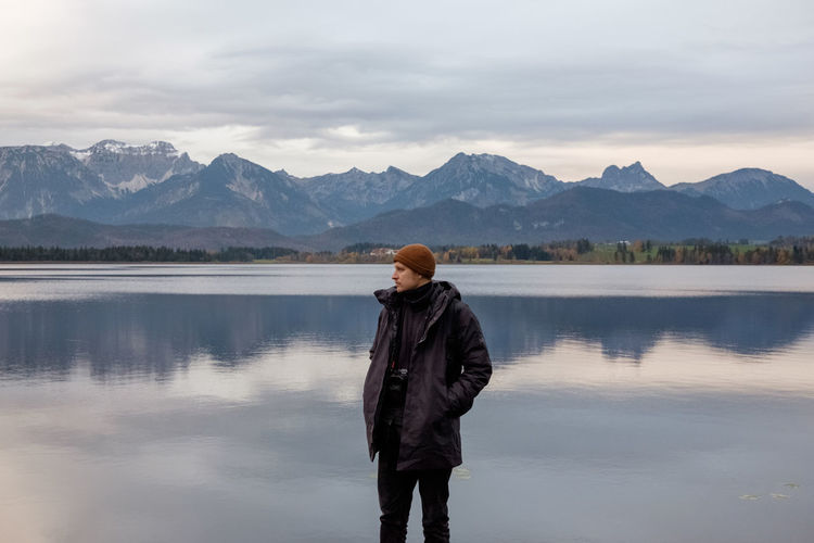 Man looking away while standing against lake