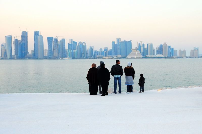 Rear view of family standing by river at mia park against city