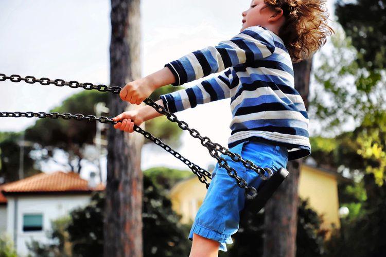Side view of boy on swing