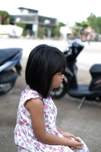 Rear view of woman with girl on car