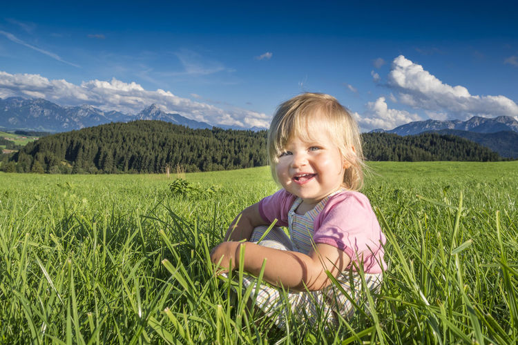 Portrait of smiling cute girl sitting on grass against sky