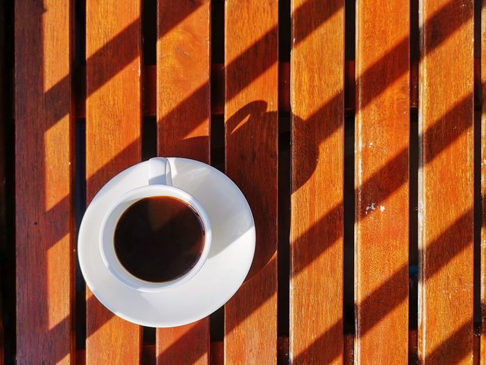 High angle view of coffee in white cup on wooden table