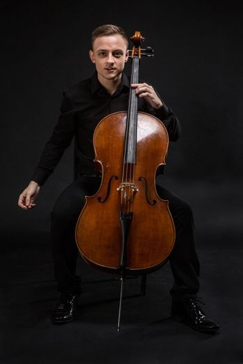 Portrait of man playing cello against gray background