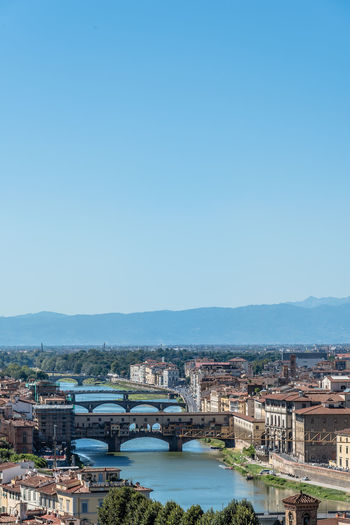 Ponte Vecchio Over Arno River Against Blue Sky In City