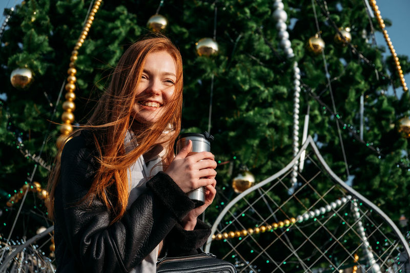 Young smiling woman holding coffee cup standing against tree