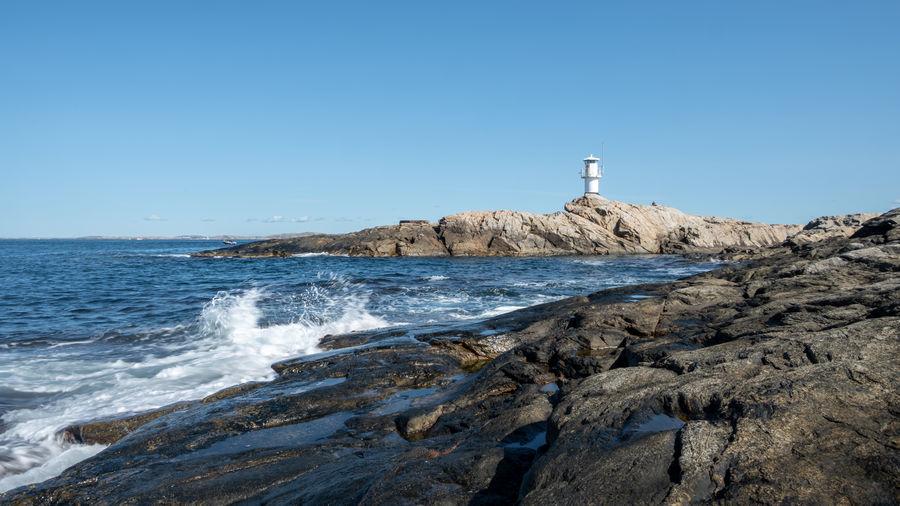 Lighthouse on rock by sea against clear blue sky