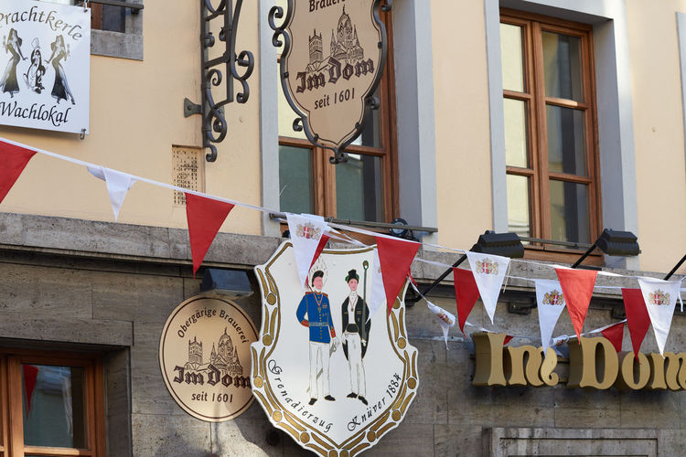 NEUSS, GERMANY - AUGUST 08, 2016: Signs indicate the age of a historic building Advertising Business Finance And Industry City Life City Street Commercial Dock Culture Downtown Historic Historic Buildings Urban History Medieval Neuss, Germany Pedestrants Shopping