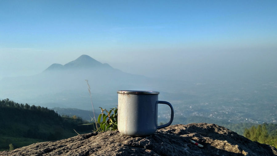 RANU KUMBOLO LAKE IN SEMERU MOUNTAIN Mountain Mug Tranquil Scene Sky Food And Drink Beauty In Nature Cup Nature Day Drink Mountain Range Scenics - Nature No People Coffee Fog Refreshment Tranquility Coffee Cup Landscape Mountain Peak
