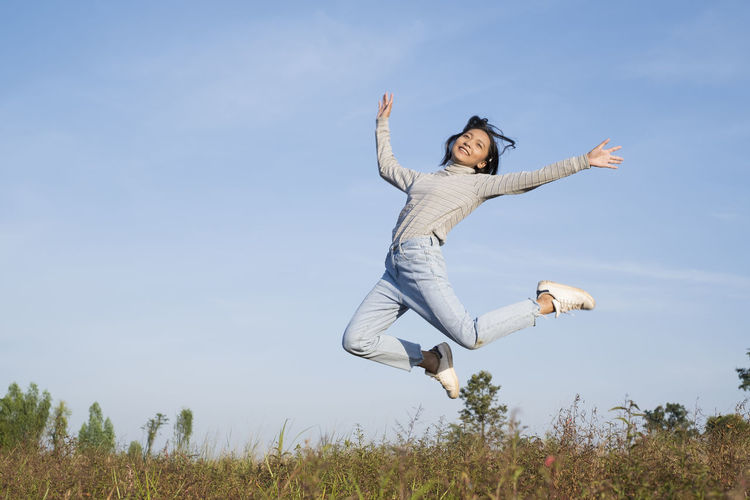 Full length of young woman jumping on field against sky