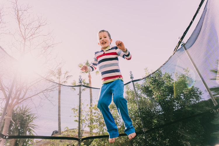 Low angle view of boy jumping on trampoline against trees