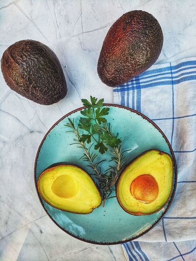 Fresh avocado with herbs and lemons lies on the table on blue plate on white background. flat lay
