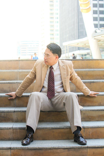 Mature businessman sitting on steps