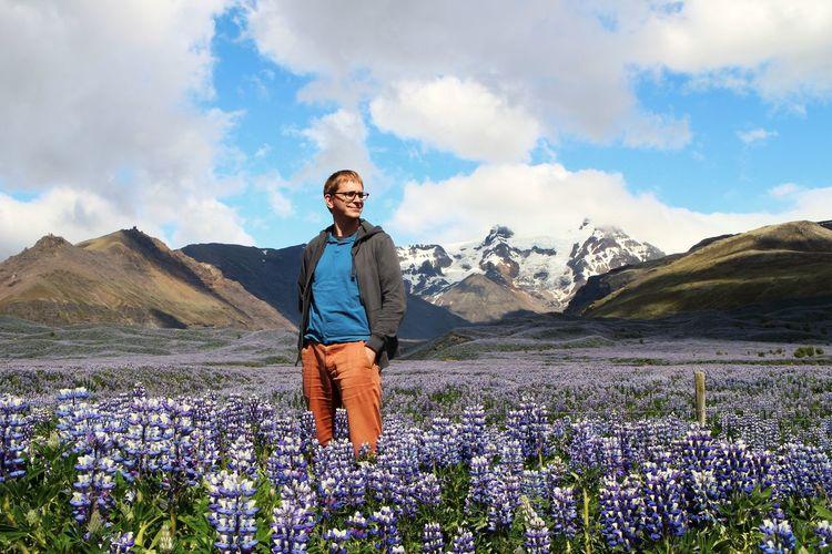 Man standing by purple flowering plants against sky