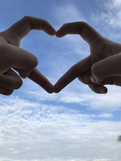 Low angle view of hand holding heart shape against sky