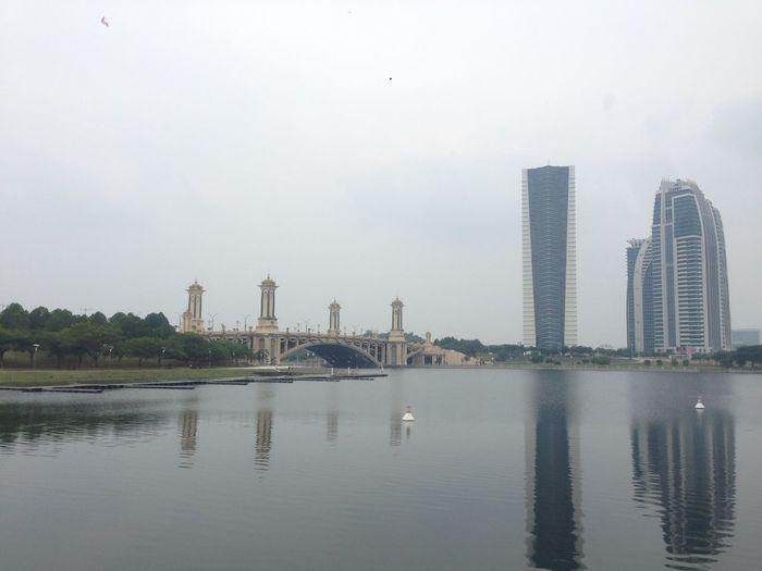 Modern buildings by lake against sky in city