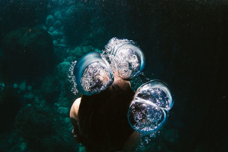 High angle of woman swimming underwater in sea amidst bubbles