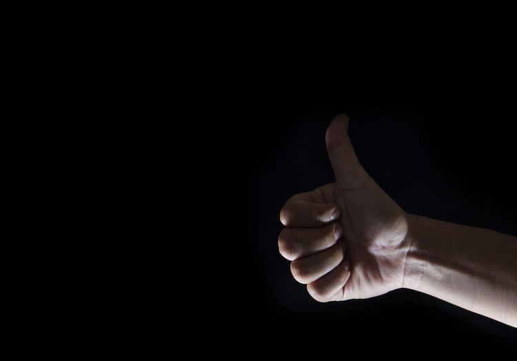 Close-up of human hand over black background