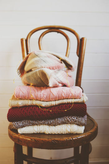warm knitted sweaters stack on wooden chair. Indoors  Still Life No People Seat Textile Chair Home Interior Wool Furniture Cozy Warm Clothing Knitted  Sweater Autumn Winter Cozy Place Knitted Sweater Stack Collection Fashion Style