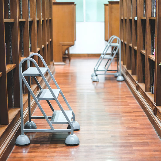 Ladders amidst bookshelves in library