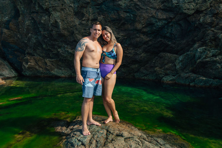Two People Rock Rock - Object Couple - Relationship Young Adult Solid Heterosexual Couple Adult Full Length Togetherness Love Men Young Men Emotion Young Women Water Leisure Activity Women Positive Emotion Young Couple Girlfriend Boyfriend Shorts Outdoors
