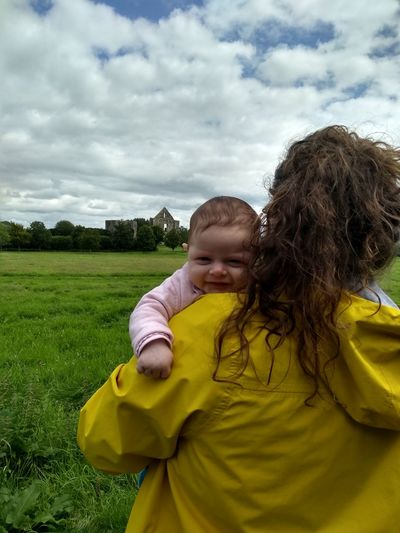 Portrait of cute girl with mother on field against sky