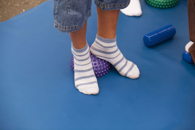 Low Section Of Child Wearing Socks Standing On Spiked Balls While Exercising In Gym
