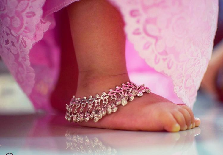 Low section of girl wearing anklet on floor