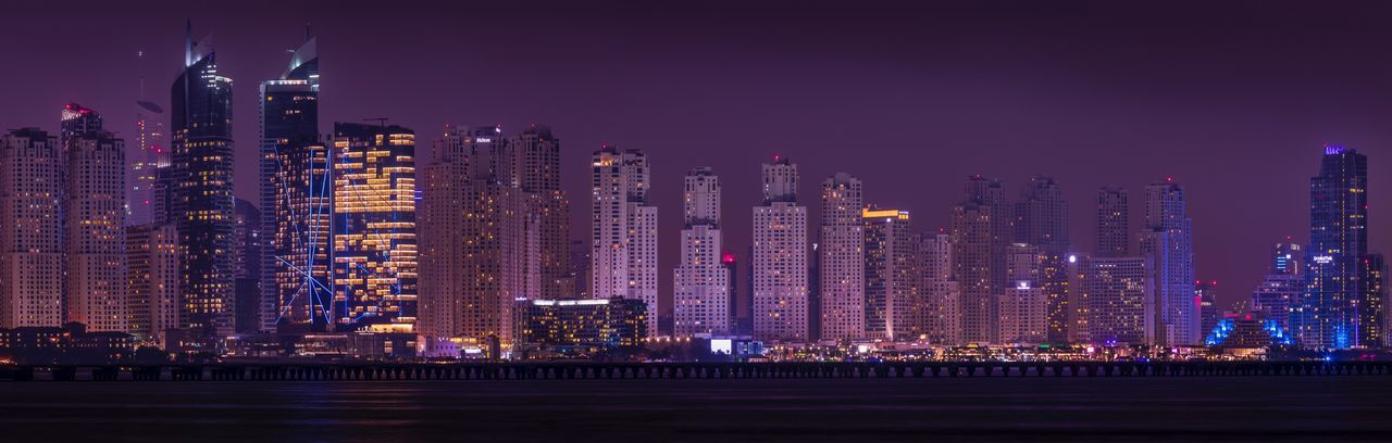 Panoramic view of illuminated cityscape against sky at night