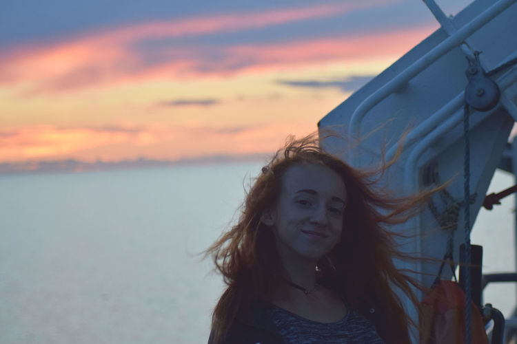 Smiling young woman against sea during sunset