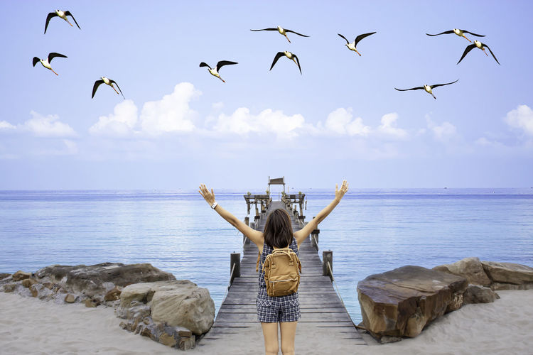 Rear view of woman with arms raised looking at sea while birds flying over beach against sky