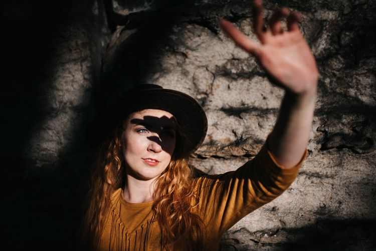 Portrait of young woman in hat standing against wall
