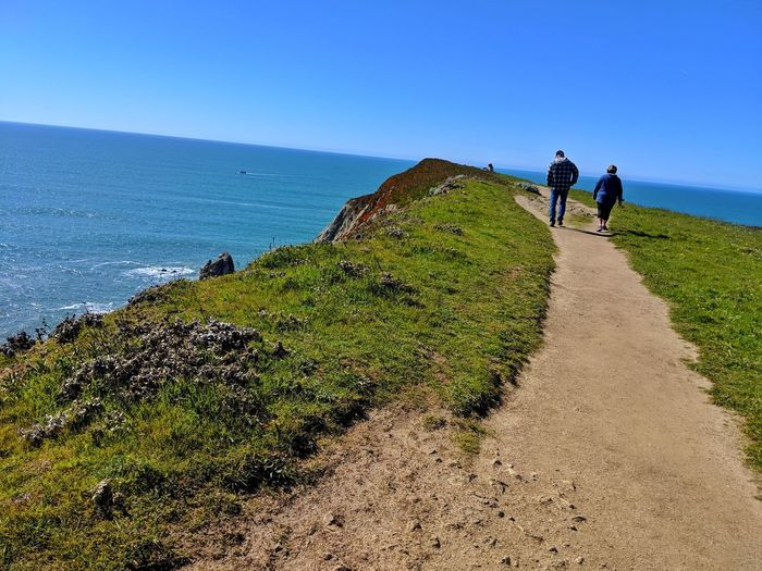 Couple walking along ocean cliffs edge path. Sandstone Blue Smartphone Overlook Edge Distance vanishing point Two Couple Man Woman Meander Strolling Hiking Exercise Therapeutic Peaceful Background Ocean Soil Water Sea Women Beach Men Hiking Togetherness Walking Sky Horizon Over Water