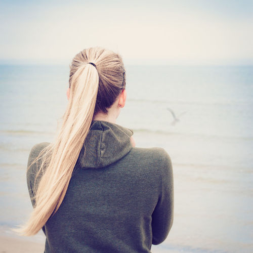 Rear View Of Blond Woman Standing At Sea Shore