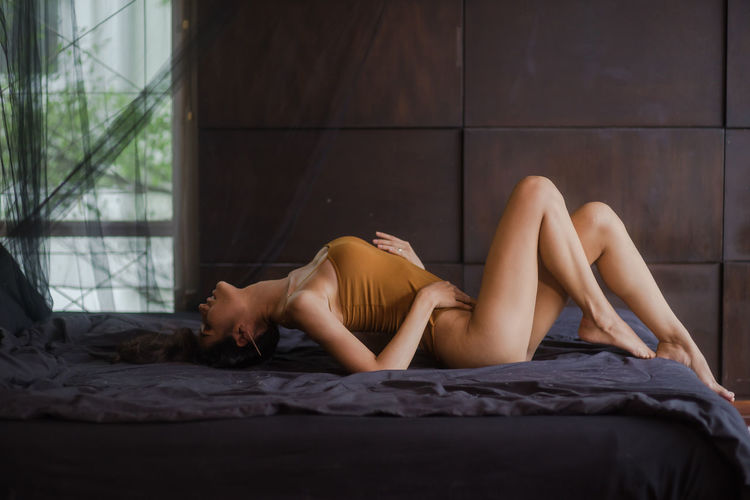 Side View Of Seductive Woman Lying On Bed At Home