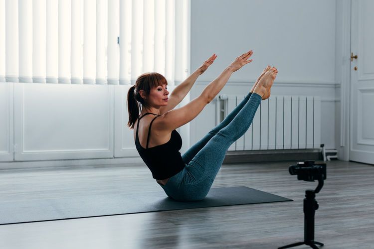 Female athlete doing gymnastic exercises on the mat using a mobile phone app.
