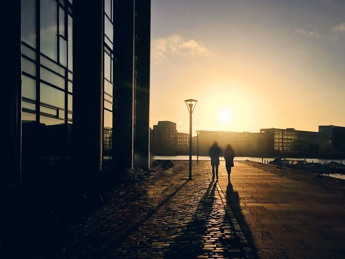 Silhouette man walking in city against sky during sunset
